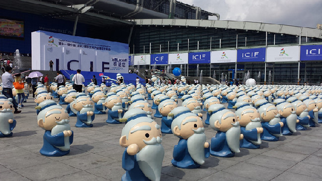 Dozens of cute Confucius cartoon statues stand in line near the entrance of the cultural fair hall.(from china culture)