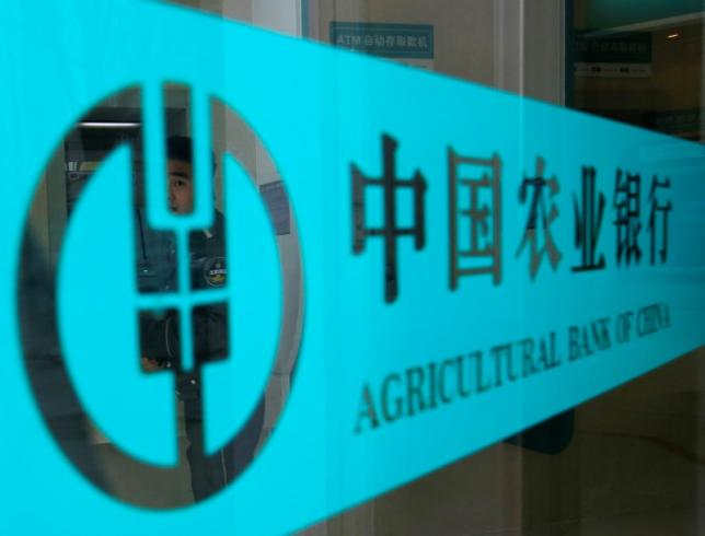 A security guard is seen through a logo of Agricultural Bank of China in Beijing April 23, 2013.  REUTERS/Kim Kyung-Hoon